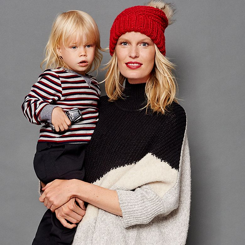Model Caroline Winberg wears a polo neck jumper and holds her toddler