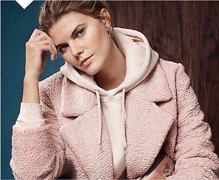 Model wears light pink hoodie with pink coat