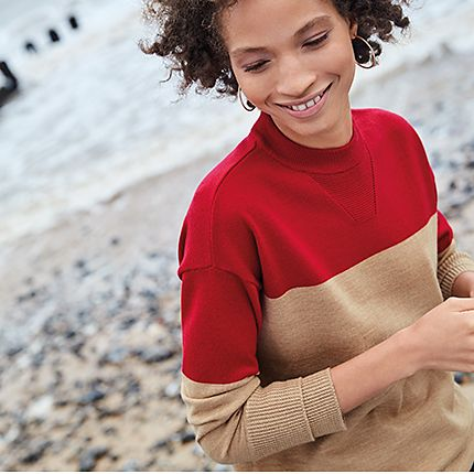 Woman on the beach wearing a red and camel jumper