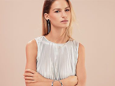 Woman wears sleeveless silver plisse dress and silver bracelet