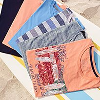 Various men's T-shirts laid on some sand