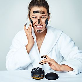 Smiling woman with charcoal soap on her face