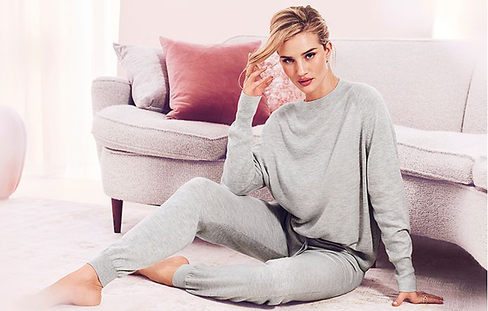 Rosie Huntington-Whiteley sitting on the floor in matching grey cashmere pyjamas
