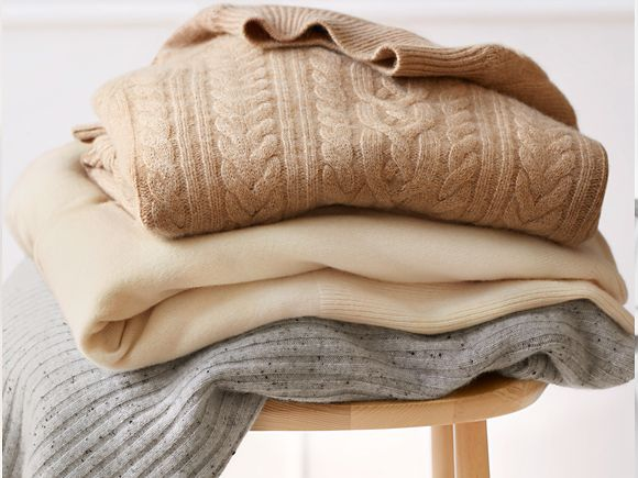 Folded cashmere jumpers on a wooden stool