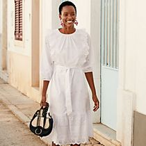 Woman wearing a white broderie-anglaise dress with a black handbag and black sandals