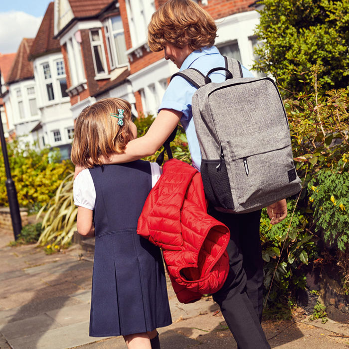 Boy and girl wearing M&S school uniform with boy wearing pale grey school rucksack