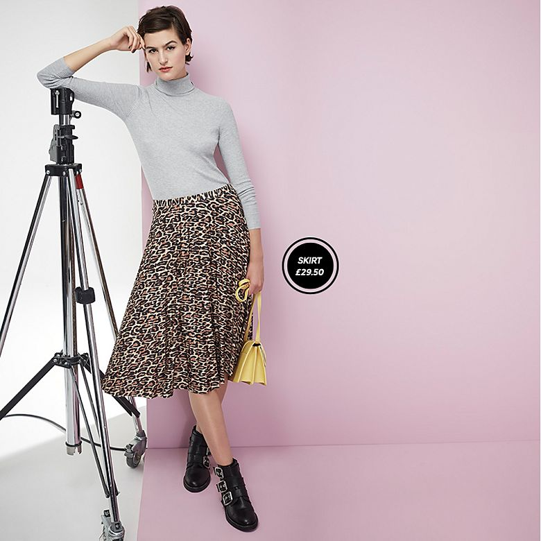 Woman wearing grey skinny-rib polo with pleated leopard-print skirt