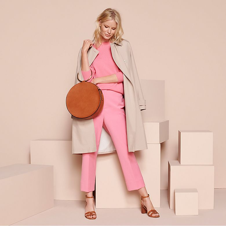Woman wearing pink cashmere jumper, pink trousers and beige trench coat