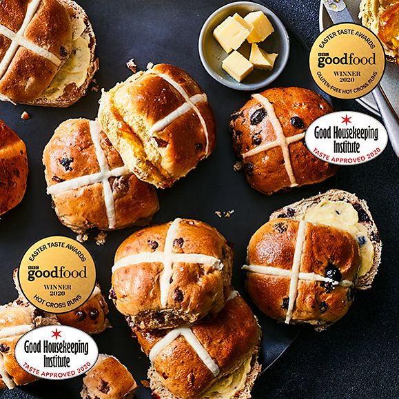 A selection of hot cross buns and a dish of cubed butter