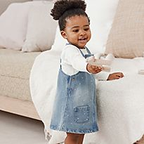 Baby girl wearing M&S denim pinny