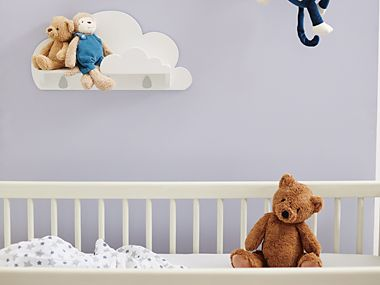 Teddy bear sitting in a cot