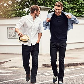Two men wearing jeans walking along a street