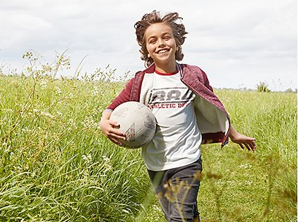Boy carrying football wearing T-shirt, jeans and cotton bomber jacket