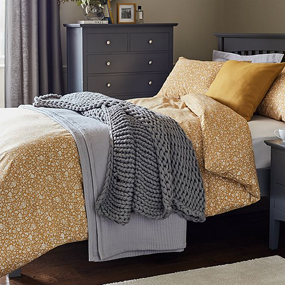 Bed with mustard printed bedding and grey throws