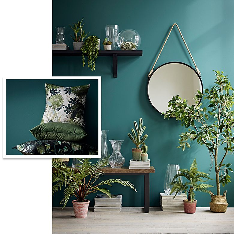 Artificial plants with a wooden mirror and patterned green cushions