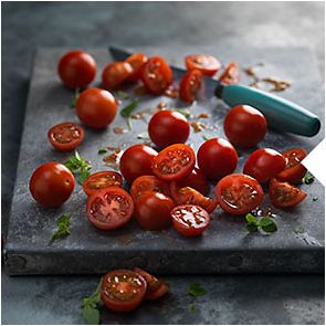 A cutting board with cherry tomatoes