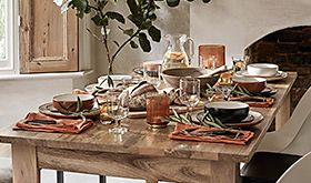Wooden dining table covered with dinnerware