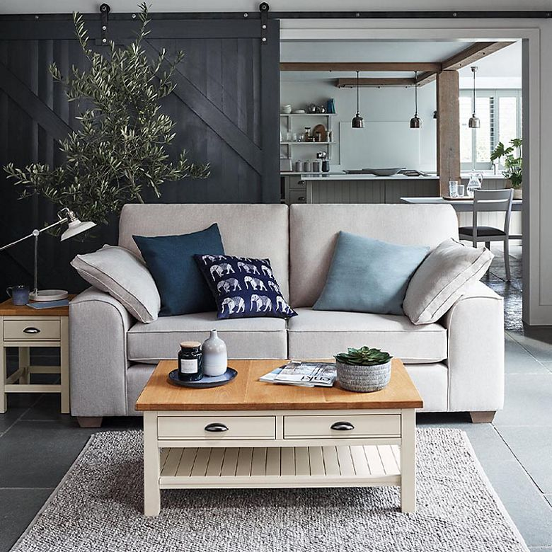 Living room with cream sofa with blue cushions, cream side table and cream coffee table