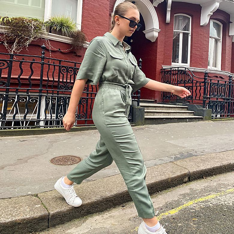 Woman wearing khaki jumpsuit and white trainers