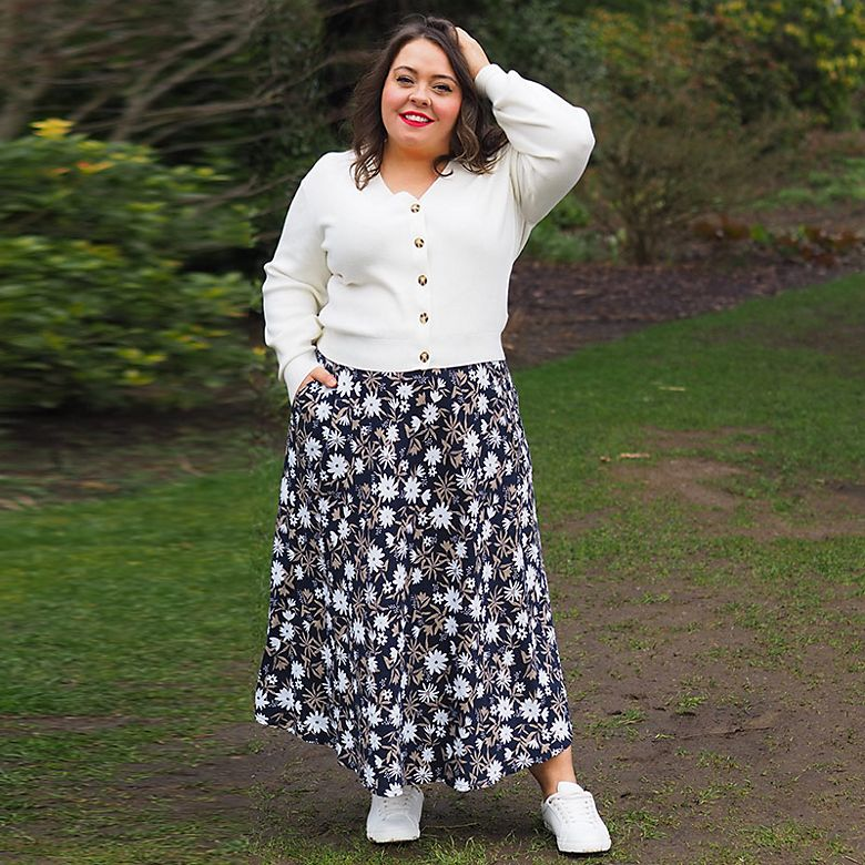 Woman wearing cream cardigan and printed floral skirt