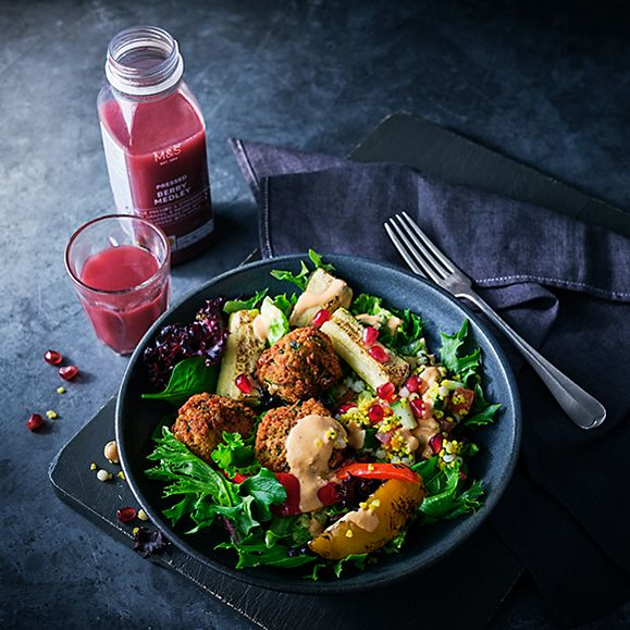 Bowl of falafel and chargrilled vegetable salad with a glass of fruit smoothie