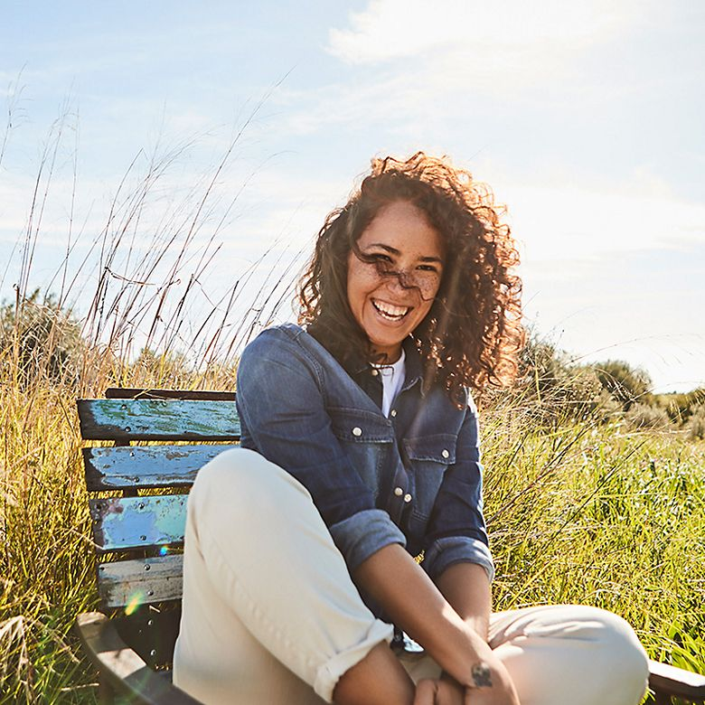 Woman wearing denim jacket and beige trousers in a meadow