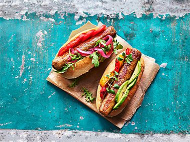 Plant Kitchen posh dogs in hot dog buns with slices of avocado, tomato and red onion
