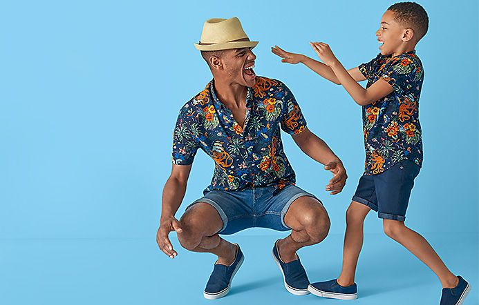 Father and son wearing matching octopus-print shirts and denim shorts