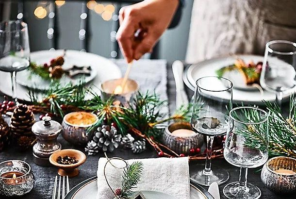 Festively set table with candles, pine cones and foliage