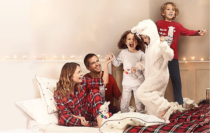 Family on a bed wears Christmas sleepwear