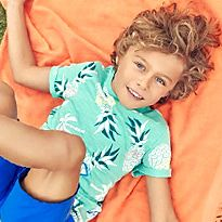 Boy lying on an orange blanket wearing a green printed T-shirt and blue shorts