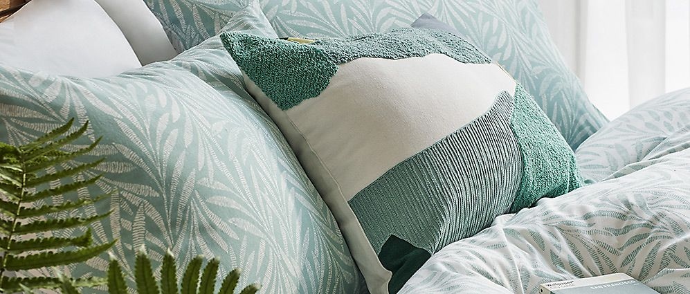 Blue, green and white bed linen on a bed