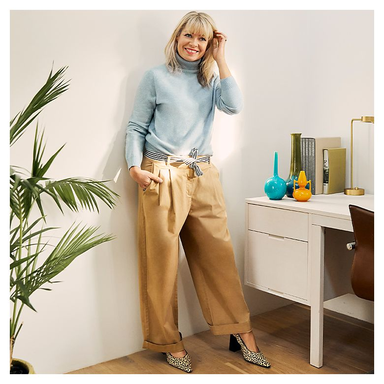 Fran Bacon wearing wide-leg chinos, blue jumper and leopard-print shoes