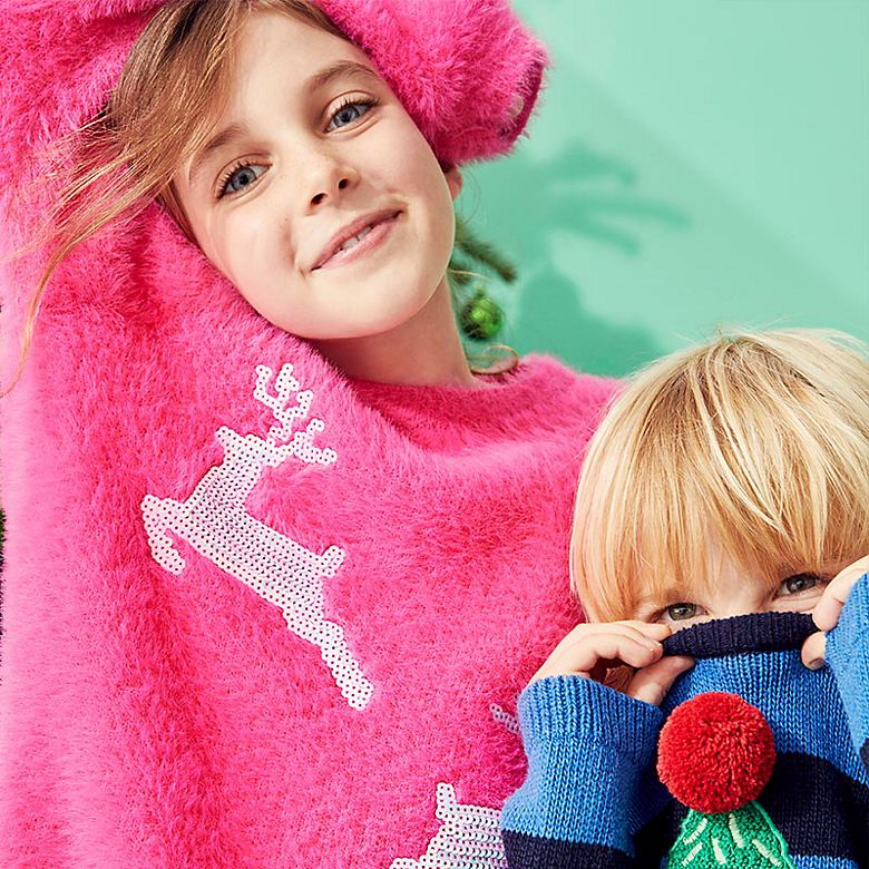 Girl wearing jumper featuring sequinned reindeer and boy wearing jumper featuring novelty Christmas tree