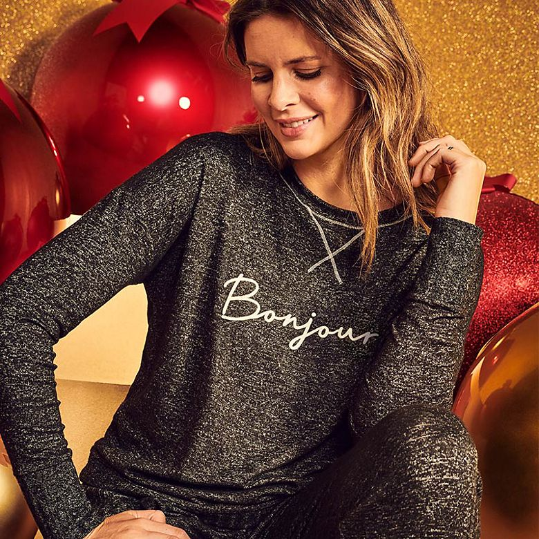 Woman wearing black marl sweatshirt with Bonjour logo and matching joggers