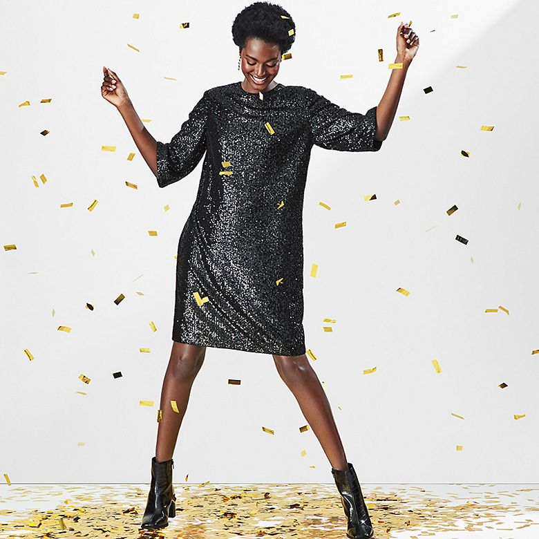 Woman dancing in knee-length sequinned black shift dress and patent ankle boots with confetti falling around her