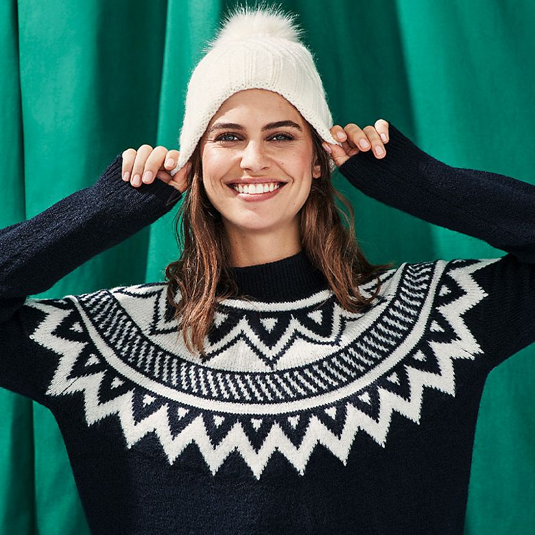Woman wearing navy and white graphic Fair Isle jumper and white bobble hat
