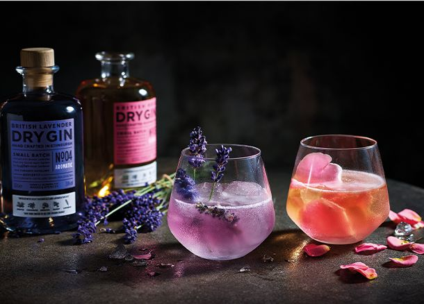 Bottles and glasses of lavender and rose colour-changing gins