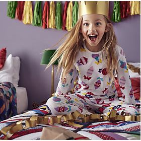 Excited girl on bed in Christmas pyjamas surrounded by Christmas decorations