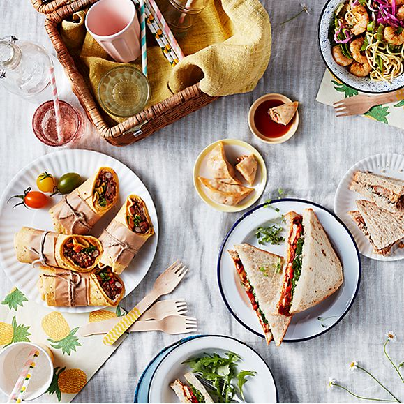 A selection of sandwiches and wraps arranged picnic-style, with a hamper on a blanket