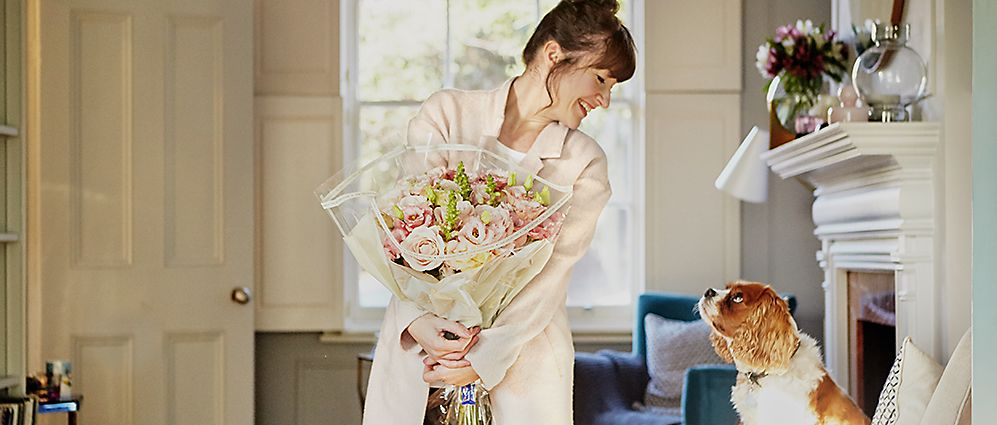 f6eee4ae73380 Melanie Lissack holding a pink bouquet smiling at her pet dog