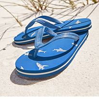 Pair of boy's blue flip flops in the sand