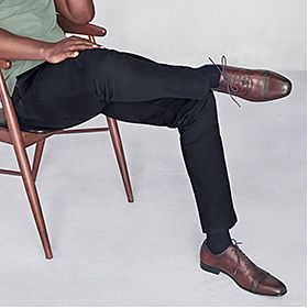 Man sitting on a chair wearing formal trousers and smart shoes