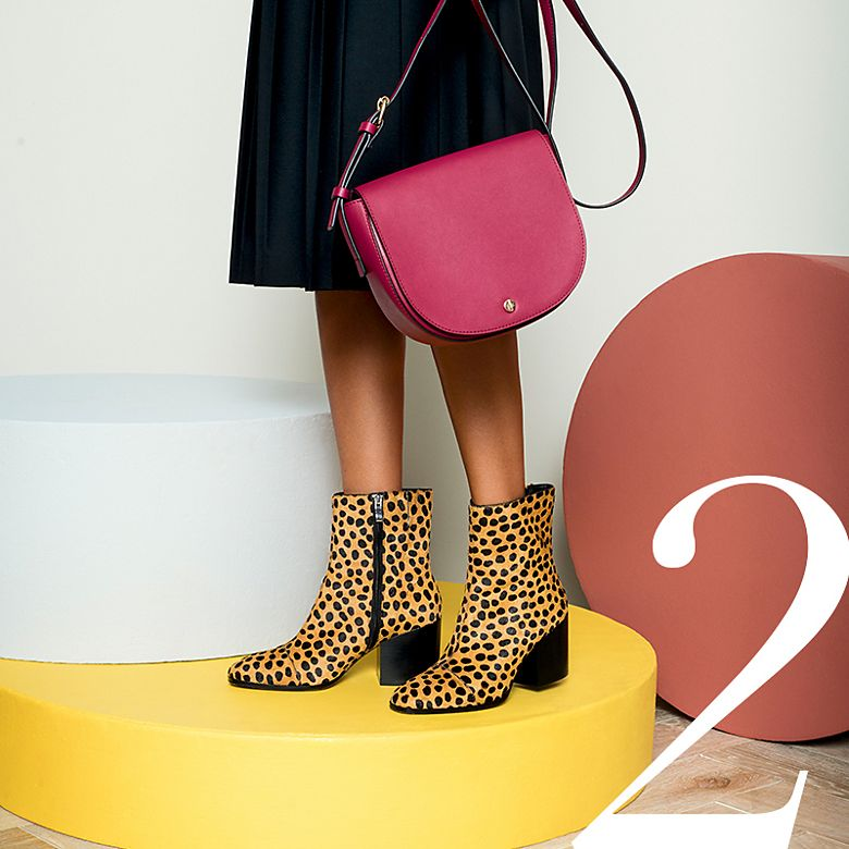 Model wears leopard-print boots with a pleated skirt and red bag