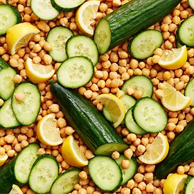 A bed of chickpeas and sliced cucumber and lemon
