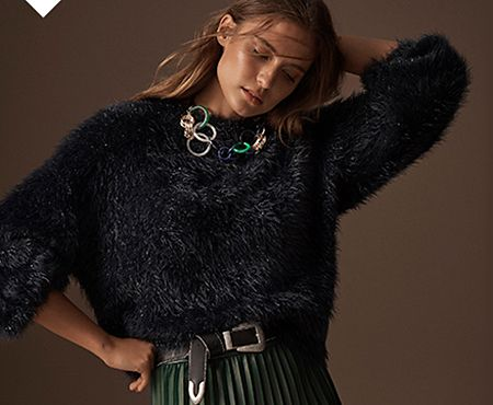 Model wears a navy faux-fur jumper over a green pleated faux-leather midi skirt with a black belt and statement necklace