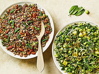 Two bowls of grain salad topped with beans and herbs