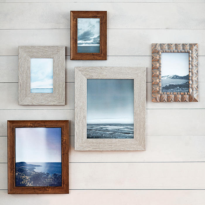 Picture frames with travel photos on a wall