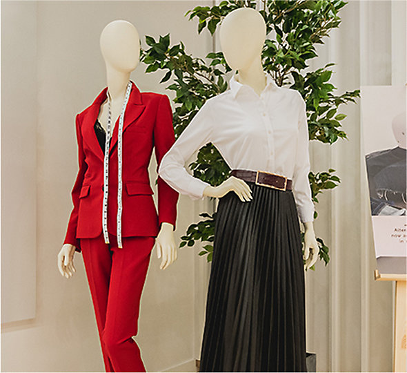 Mannequins dressed in a red suit and a white shirt and black pleated skirt