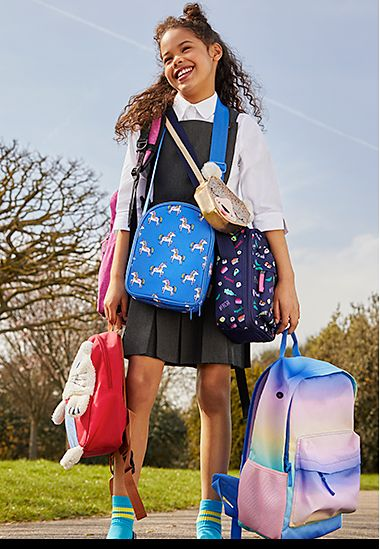 Girl in school uniform carrying a collection of school bags